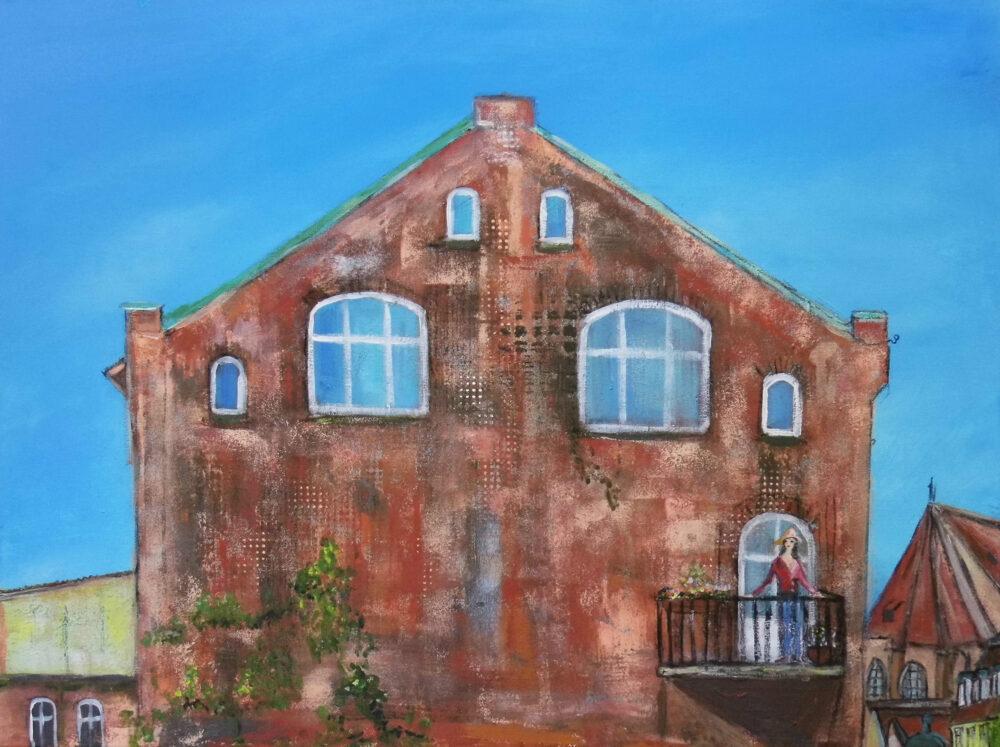 """Das Bild zeigt eine Frau mit rotem Pullover und Sonnenhut auf dem Balkon eines real existierenden Backsteinhauses der Strasse """"Auf dem Meere"""" in Lüneburg. Man sieht einen kleinen Teil der St. Michaeliskirche und den blauen Sommerhimmel."""